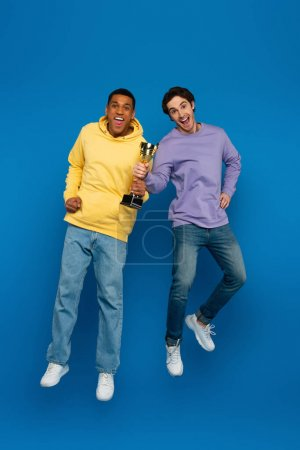 Photo for Happy african american man with friend levitating and holding triumph cup  in hands on blue background - Royalty Free Image