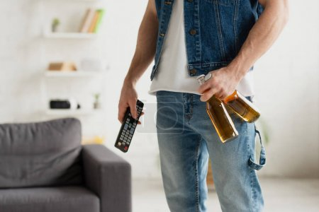 Photo for Cropped view of man with beer bottles and tv remote controller in hands on blurred background - Royalty Free Image
