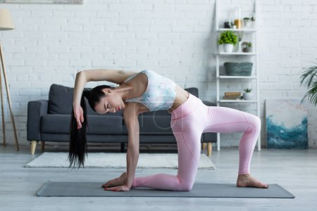 Photo for Flexible woman practicing side plank on knee pose on yoga mat - Royalty Free Image