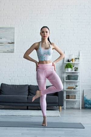 young woman standing on one leg with hands on hips while practicing yoga