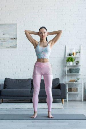 Frau in Sportkleidung steht in Berg-Pose vor der Kamera
