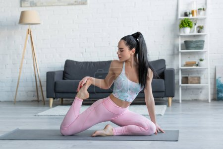 pretty, sportive woman practicing mermaid pose at home