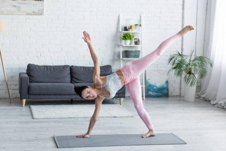 Photo pour Sportif pieds nus femme pratiquant planche latérale star pose sur tapis de yoga à la maison - image libre de droit