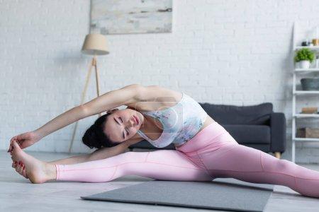 Photo pour Jeune femme les yeux fermés pratiquant la pose de la tête au genou à la maison - image libre de droit