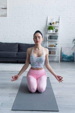 Photo pour Jeune femme en vêtements de sport méditant en héros pose sur tapis de yoga - image libre de droit