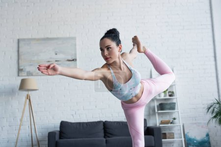 Photo for Brunette woman practicing yoga in lord of dance pose at home - Royalty Free Image