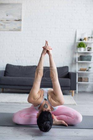 Photo pour Brunette, femme tatouée pratiquant la pose d'angle liée à la maison - image libre de droit