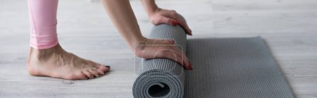 Photo for Cropped view of barefoot woman unrolling yoga mat on floor, banner - Royalty Free Image