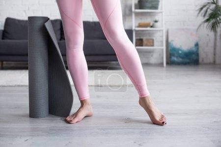 Photo pour Vue recadrée de femme pieds nus en leggings debout près du tapis de yoga à la maison - image libre de droit