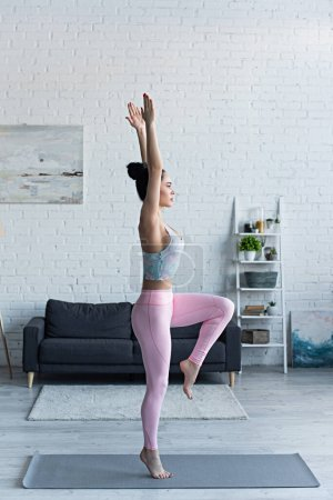 Photo for Side view of brunette woman standing on one leg with raised hands while practicing yoga - Royalty Free Image