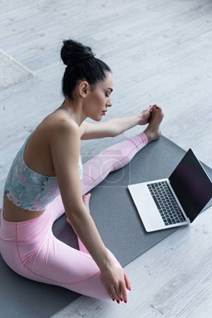 sportive woman stretching in yoga pose near laptop with blank screen