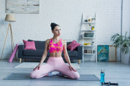 brunette woman in sports bra and leggings looking away while sitting on fitness mat