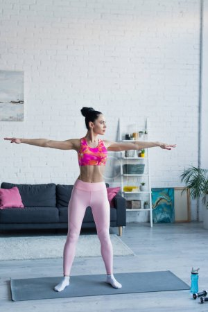 sportive woman standing in five pointed star pose on fitness mat at home