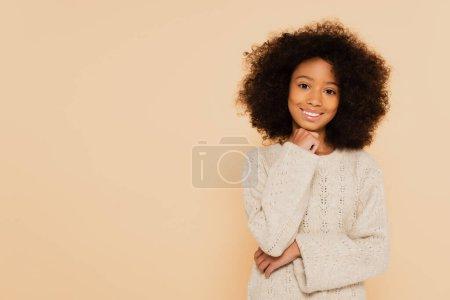 sonriente preadolescente afroamericano chica con la mano cerca de la cara aislado en beige