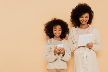 Photo for Smiling african american preteen daughter and adult mother holding cellphone and tablet in hands isolated on beige - Royalty Free Image