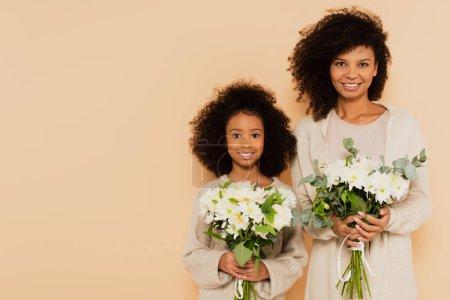 hija preadolescente afroamericana y madre adulta sosteniendo ramos de margaritas aisladas en beige