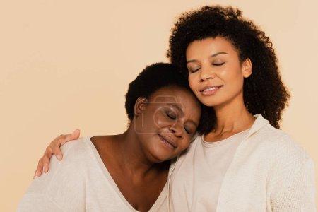 ruhige afrikanisch-amerikanische erwachsene Tochter und Mutter mittleren Alters umarmen sich mit geschlossenen Augen isoliert auf beige