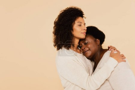 african american adult daughter hugging middle aged mother with closed eyes isolated on beige