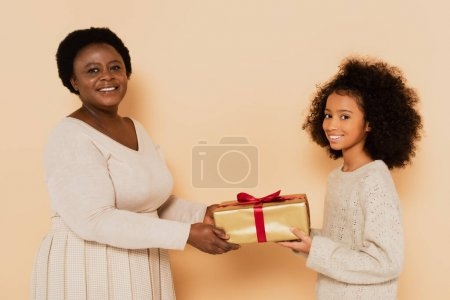 excited african american granddaughter and grandmother holding gift box and looking at camera on beige background