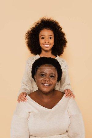 fröhliche afrikanisch-amerikanische Enkelin mit Großmutter isoliert auf beige