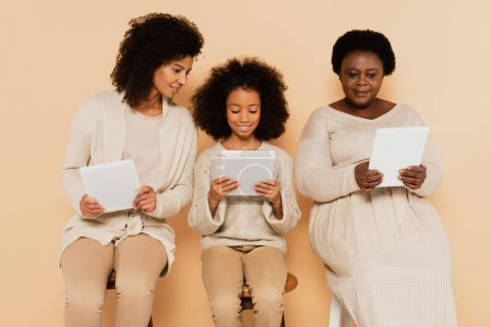 african american daughter, granddaughter and grandmother sitting and looking at tablets on beige background