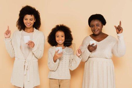 Photo pour Afro-américaine fille, petite-fille et grand-mère pointant vers le haut avec les doigts et tenant les téléphones cellulaires sur fond beige - image libre de droit