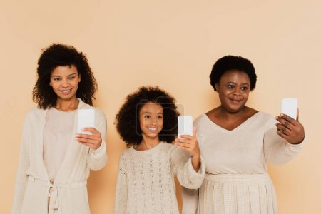 Afrikanisch-amerikanische Tochter, Enkelin und Großmutter machen Selfies auf Mobiltelefonen auf beigem Hintergrund