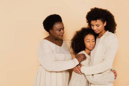 Photo pour Afro-américaine mère et grand-mère étreignant et soutenant triste petite-fille sur fond beige - image libre de droit