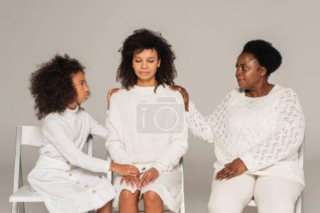Photo pour Femme adulte afro-américaine déçue assise entre la fille préadolescente et la mère d'âge moyen isolée sur gris - image libre de droit