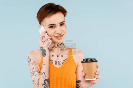 Photo for Smiling and tattooed woman talking on smartphone while holding coffee to go isolated on blue - Royalty Free Image