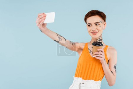 Photo for Smiling and tattooed woman taking selfie on smartphone while holding coffee to go isolated on blue - Royalty Free Image