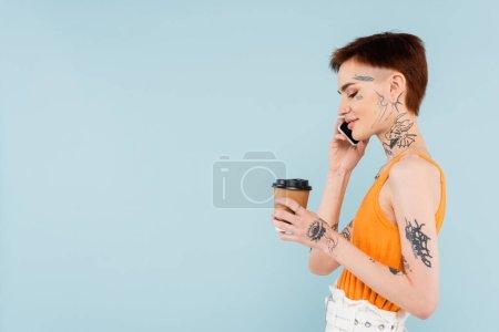 Photo pour Vue latérale de la femme souriante et tatouée parlant sur smartphone tout en tenant la tasse en papier isolée sur bleu - image libre de droit