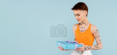 young tattooed woman looking at wrapped present isolated on blue, banner