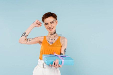 Photo pour Excité et tatoué femme tenant boîte cadeau enveloppé isolé sur bleu - image libre de droit