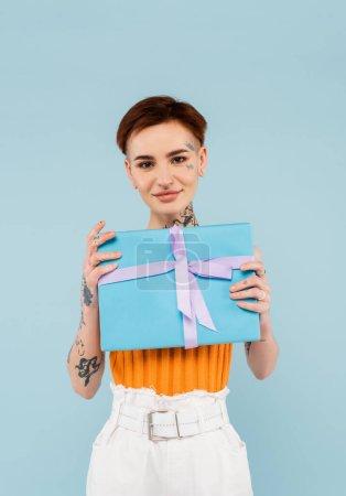 jeune femme tatouée tenant présent enveloppé et souriant isolé sur bleu