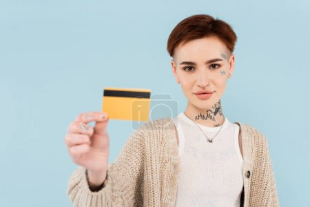 Photo for Young tattooed woman holding blurred credit card isolated on blue - Royalty Free Image