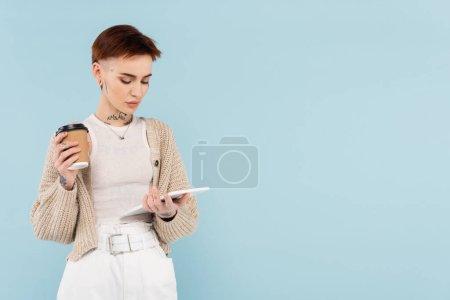 mujer joven con tatuajes sosteniendo tableta digital y taza de papel aislados en azul
