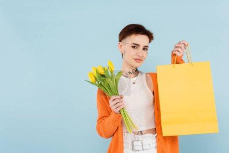 joven mujer tatuada en cárdigan naranja sosteniendo tulipanes amarillos y bolsa aislada en azul