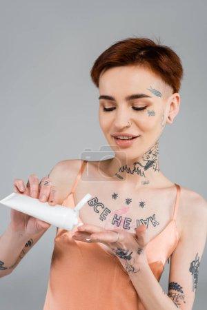 Photo pour Jeune femme heureuse avec des tatouages tenant le tube et appliquant une lotion corporelle tout en souriant isolé sur gris - image libre de droit