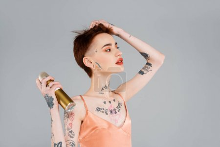 young tattooed woman with red lips using hairspray isolated on grey