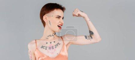 Photo pour Jeune femme tatouée avec des lèvres rouges montrant le muscle isolé sur gris, bannière - image libre de droit