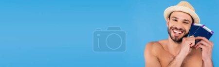 Photo pour Homme torse nu et souriant avec un chapeau de soleil et des passeports avec des billets d'avion isolés sur une bannière bleue - image libre de droit