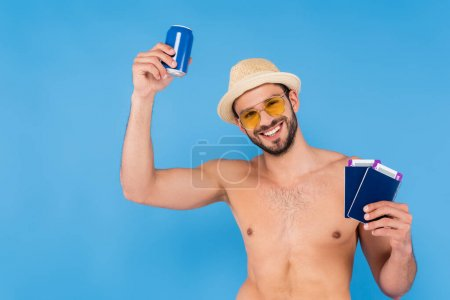 Smiling shirtless man in sun hat holding passports and canned drink isolated on blue