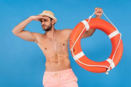 Muscular man in sun hat holding life buoy and looking away isolated on blue