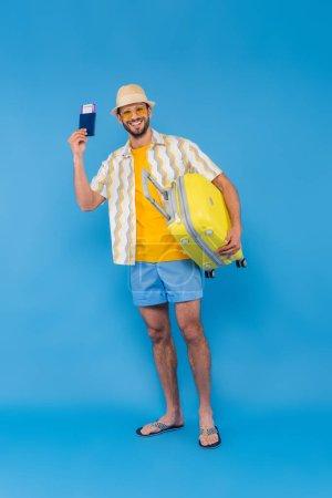Fröhlicher Mann mit Sonnenhut mit Pass und Koffer auf blauem Hintergrund