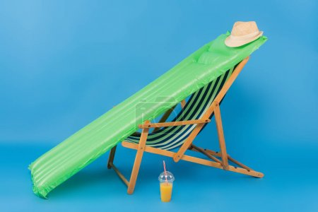Sun hat on inflatable mattress near deck chair and orange juice on blue background