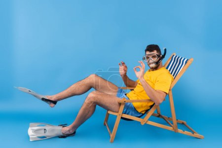 Man in swimming goggles and flippers showing ok gesture on deck chair on blue background