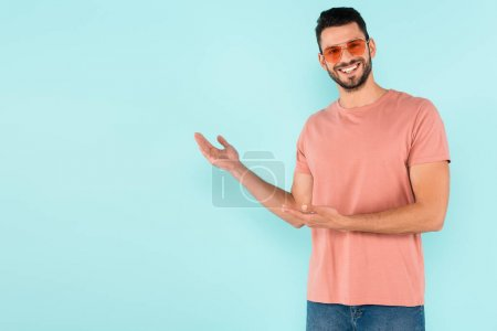 Smiling man in sunglasses pointing with hands isolated on blue