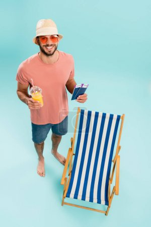 Photo for High angle view of positive man in sunglasses holding orange juice and passports near deck chair on blue background - Royalty Free Image