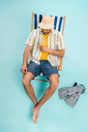 Photo pour Vue grand angle de l'homme en chapeau de paille tenant le jus d'orange près des nageoires sur fond bleu - image libre de droit